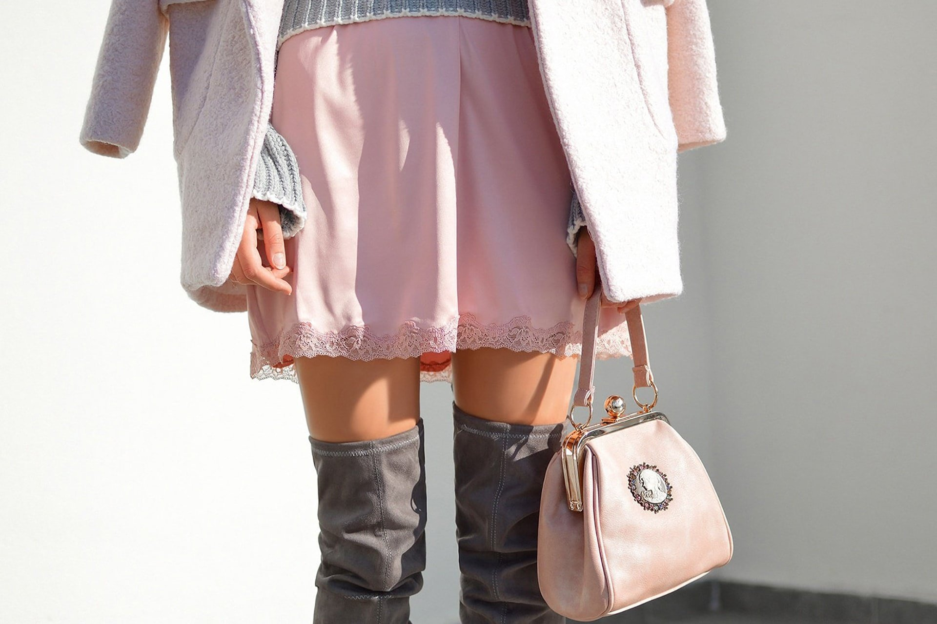 Woman wearing a pink dress and grey boots