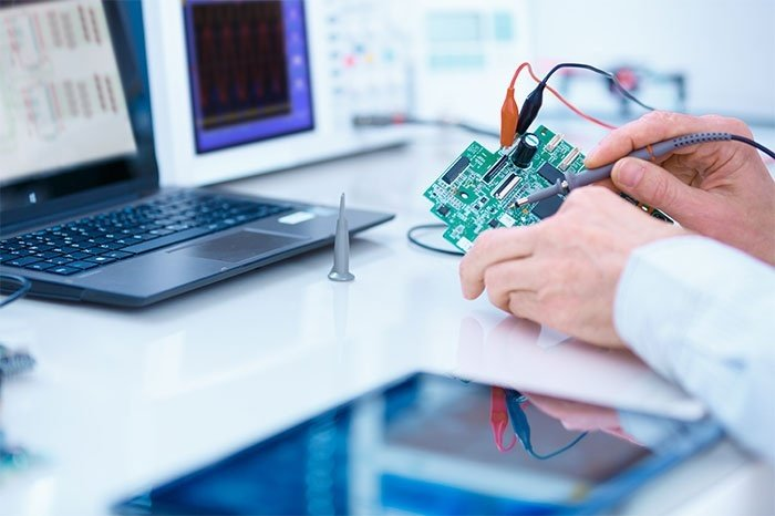 Technician holding a circuit board in front of a laptop