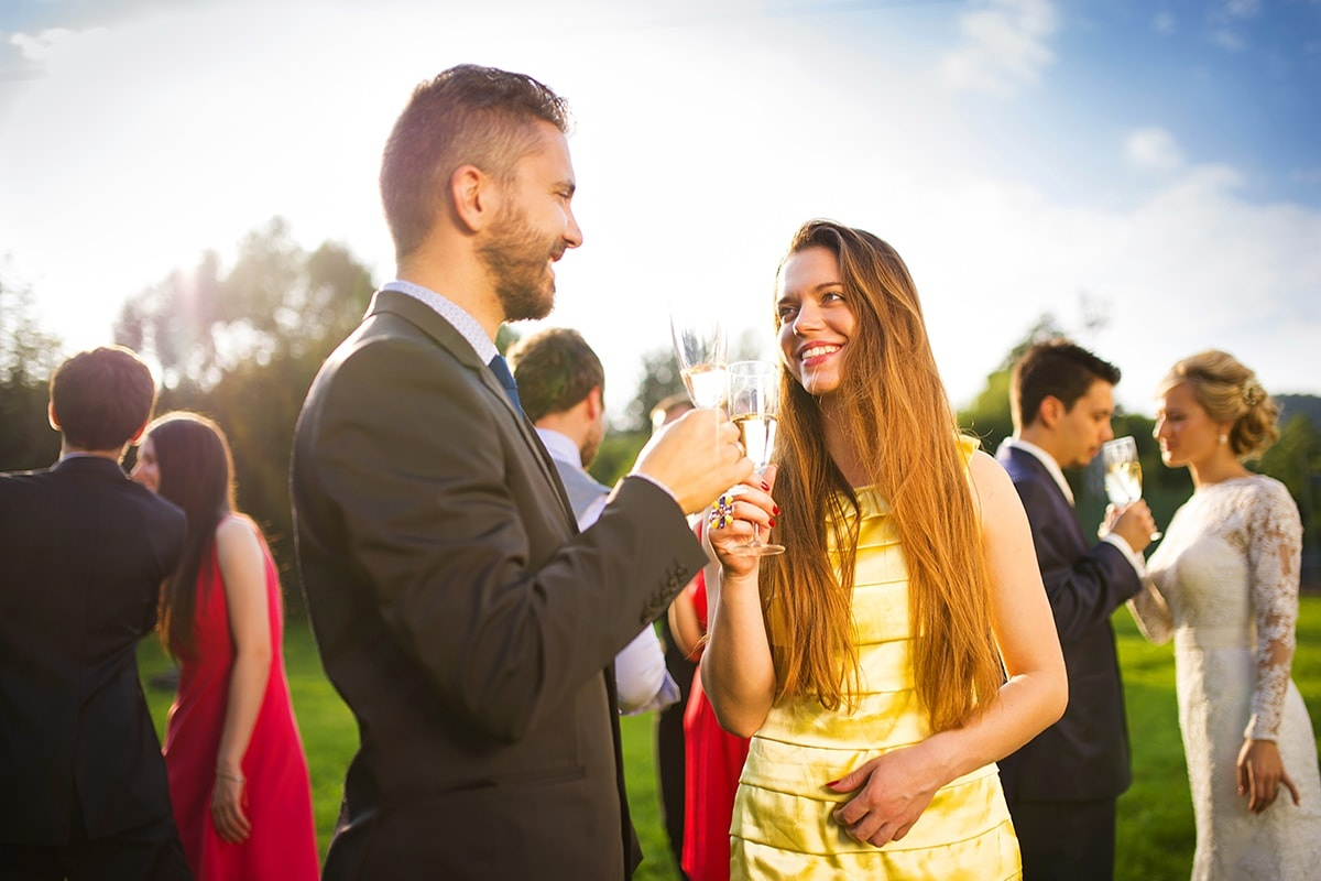Man and woman drinking champagne at a wedding