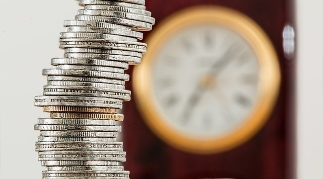 Stack of coins in front of a clock