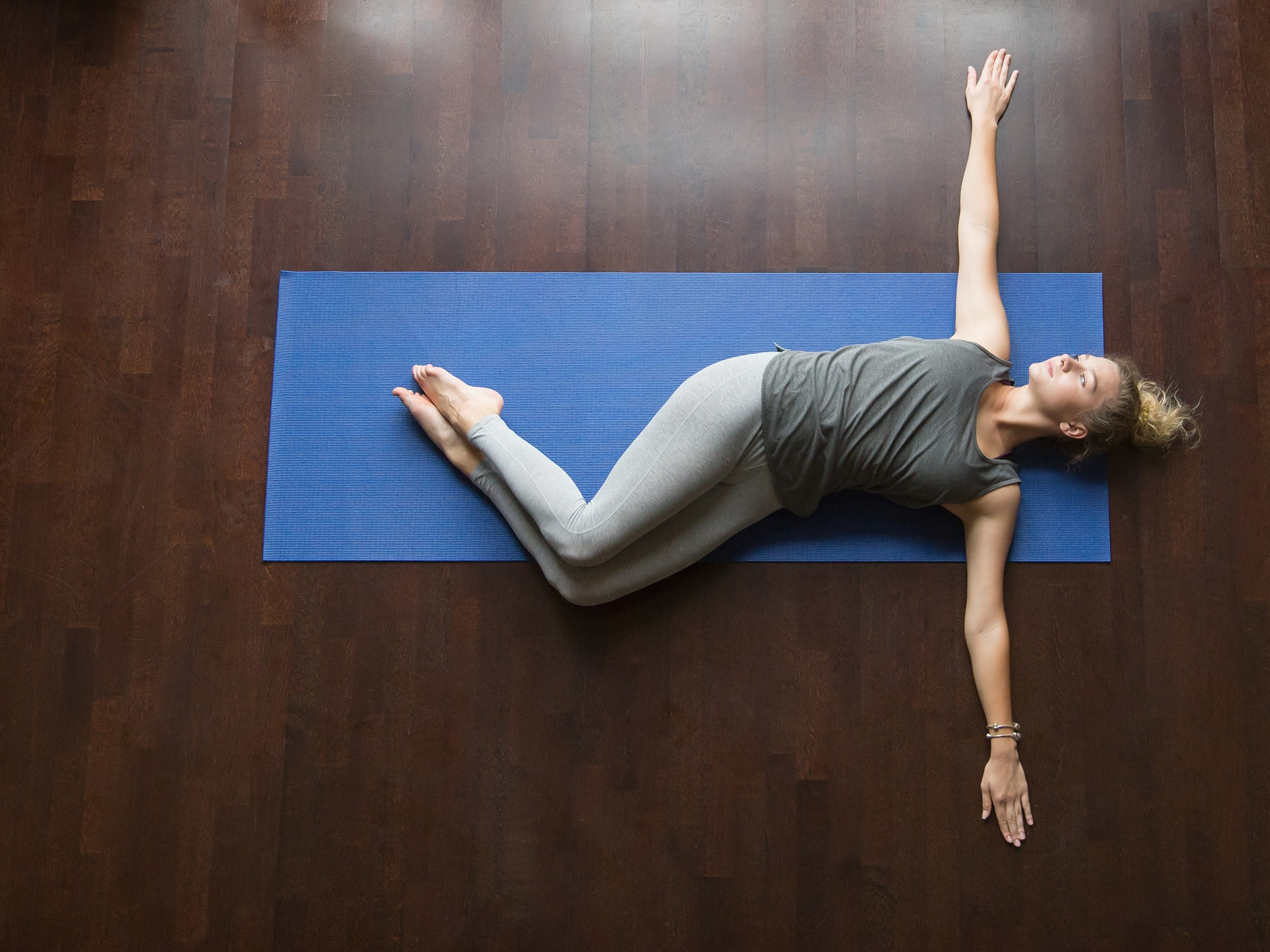 Young woman doing abdominal twist yoga pose