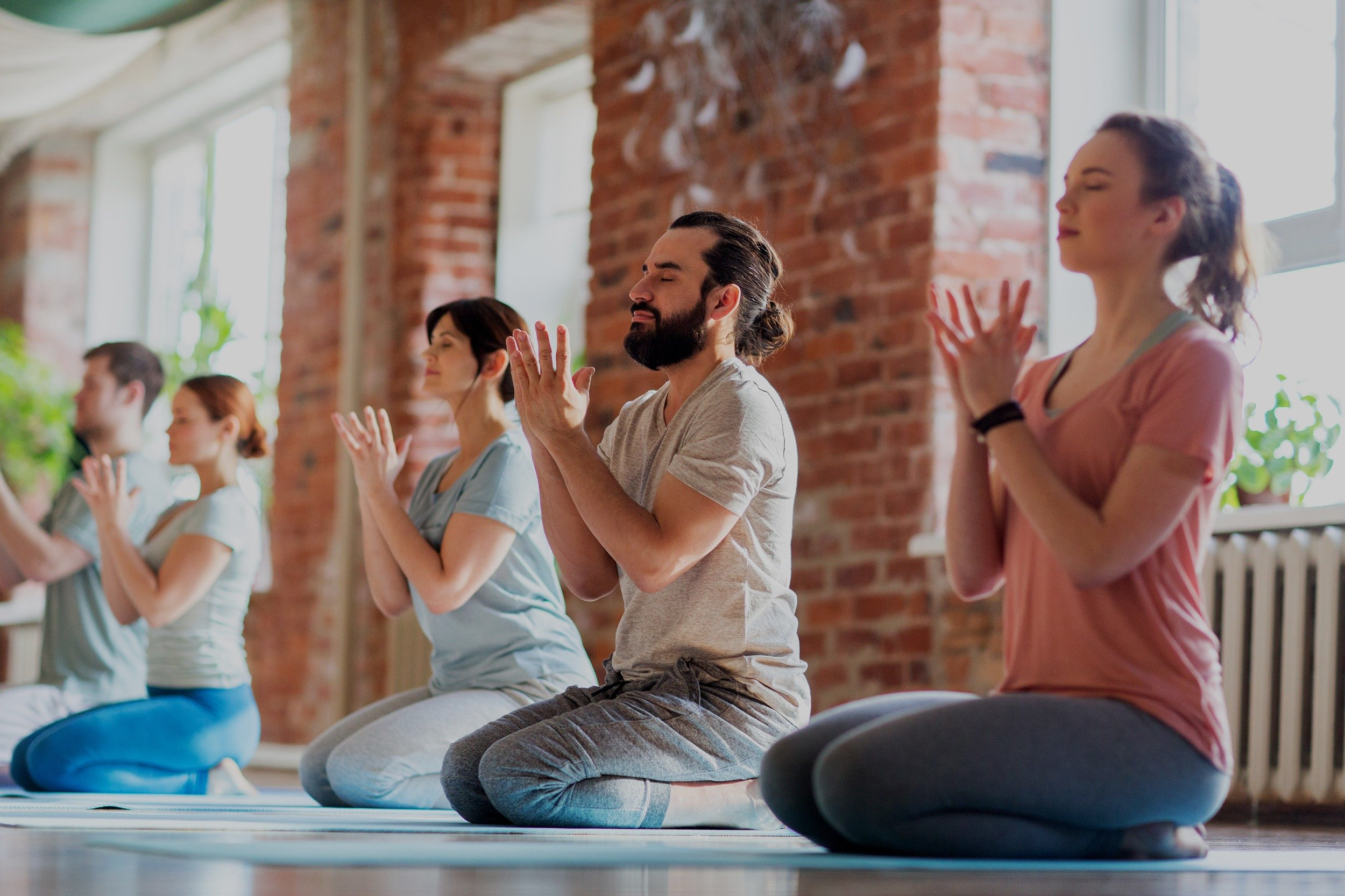 Group of people meditating at a yoga studio