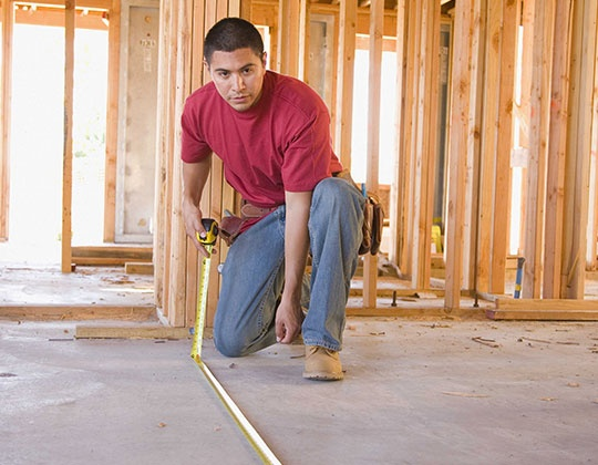 Construction worker measuring with a tape measure
