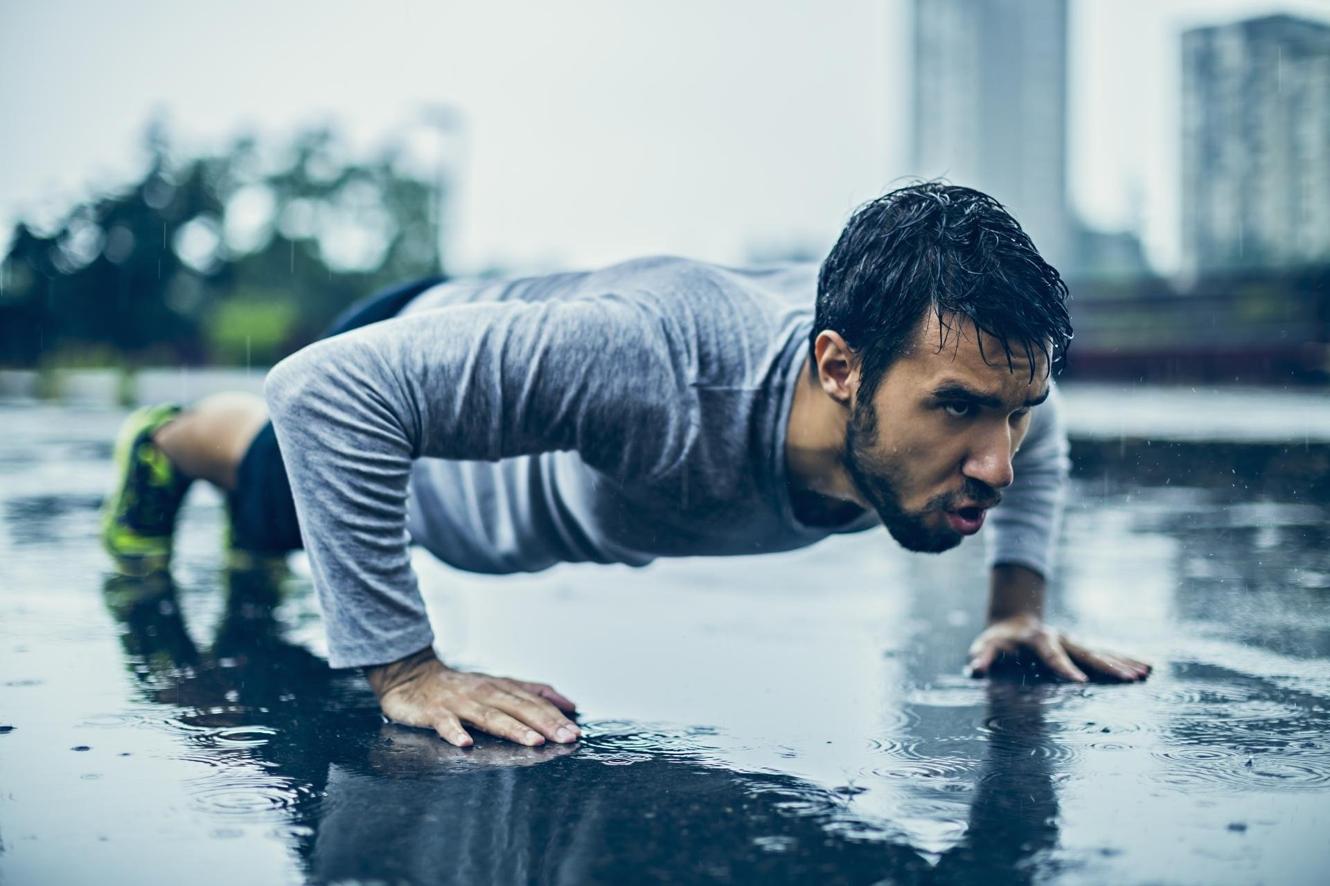 Young athletic man exercising in the rain