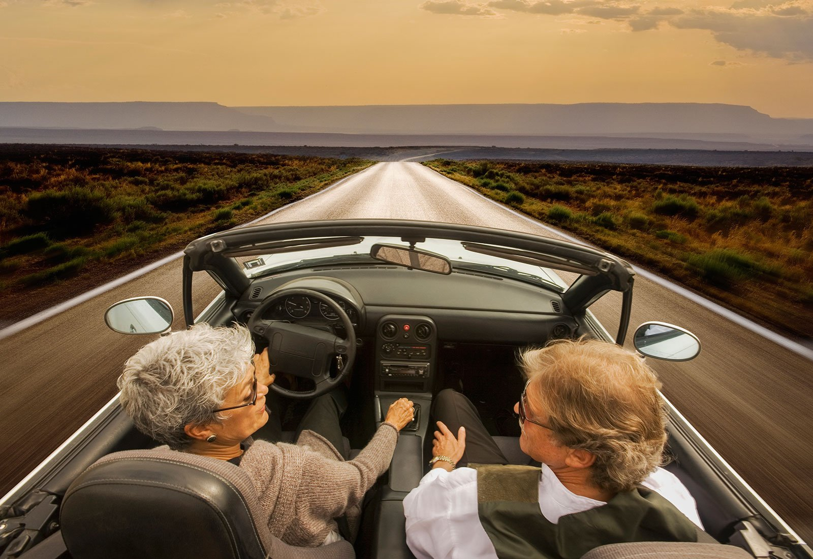 Elderly couple driving a convertible car