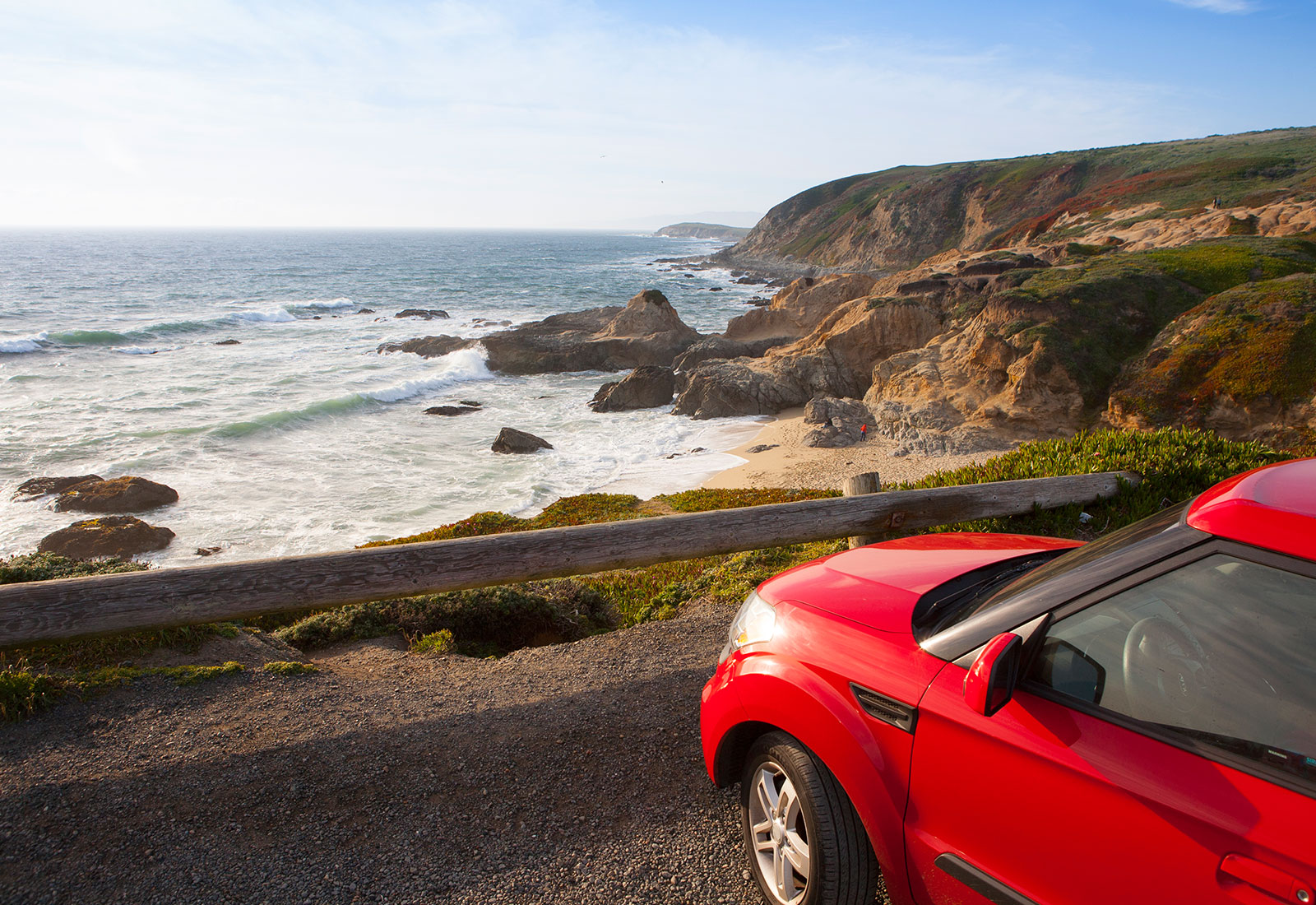 Red car in front of a sea landscape