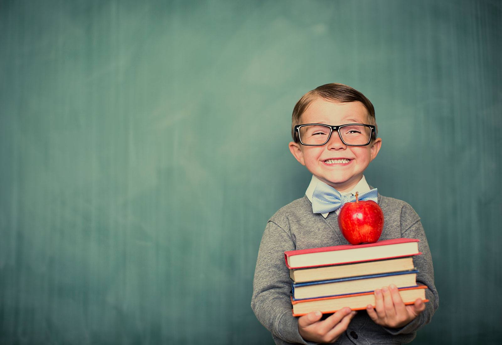 Happy child with glasses holding books and an apple on top