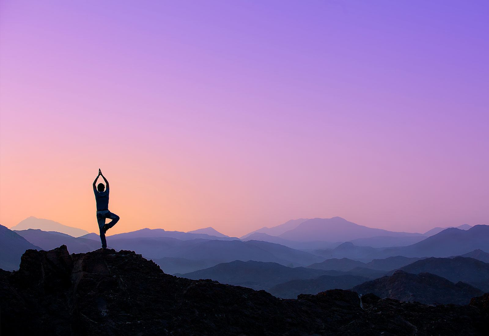 Person doing yoga on a mountain hill