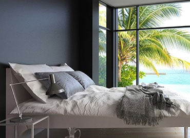 Bedroom with grey walls, large double bed and a sea view