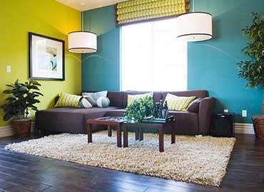 Living room with dark wood floor, brown sofa and colourful walls
