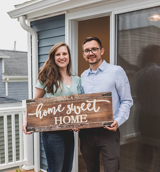 """Smiling people holding a wooden board with the inscription """"Home sweet home"""""""