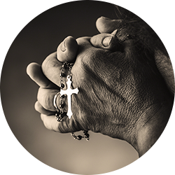 Person holding a silver cross pendant