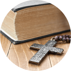 Rosary with a wooden cross next to the Bible