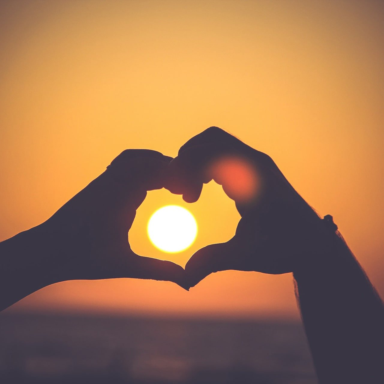 Hands forming a heart shape at sunrise