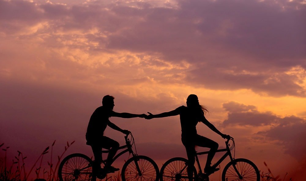 A boy and a girl riding bikes at sunset