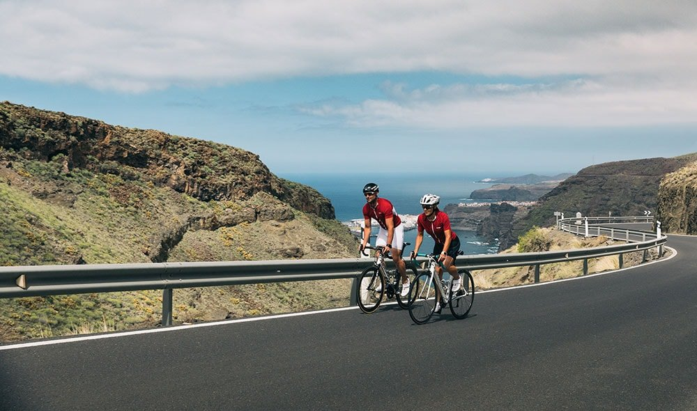 Two cyclists riding bikes on the road