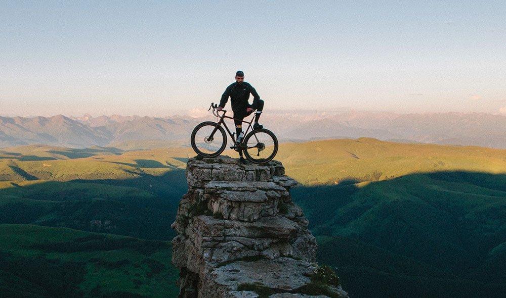 A man with a bike on a rock