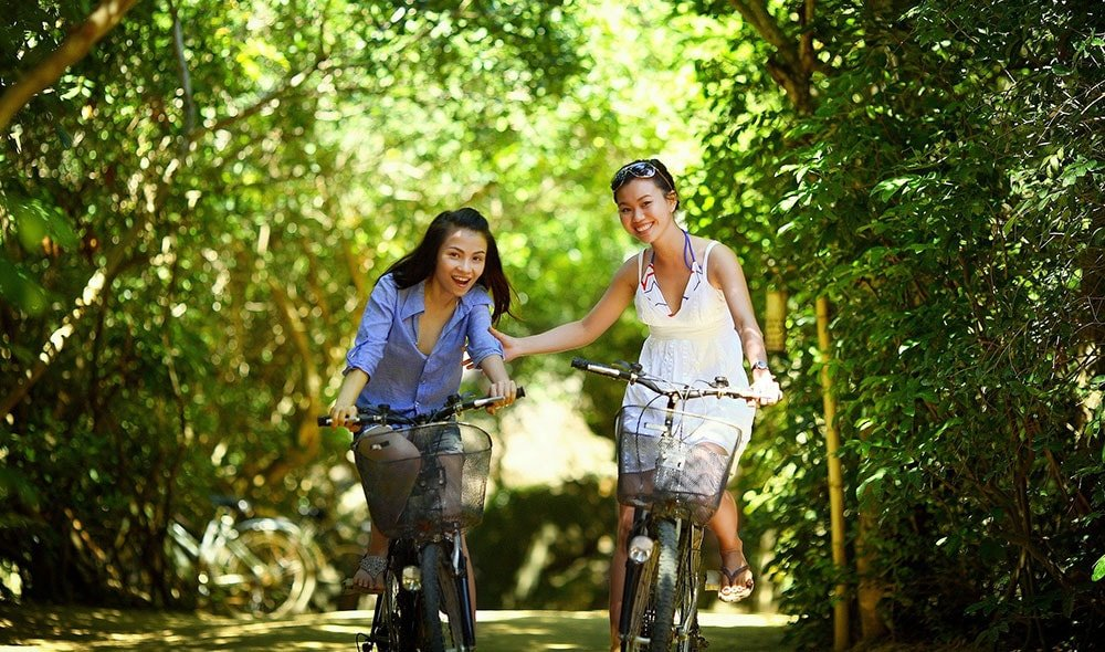 Two ladies riding bikes in a park